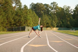 Yoga at the track; triangle pose before running; photo by Wes Rountree