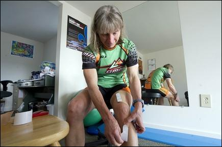 Jeb Wallace-Brodeur / Staff Photo Physical therapist and athlete Donna Smyers applies kinesio tape to her knee at her office in Adamant.